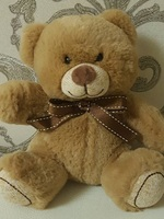 Soft toy teddy bear with bow, light brown
